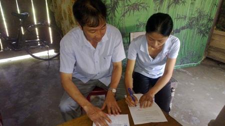 Chị Thơ, mẹ bé Huân, làm thủ tục tiếp nhận 60 triệu đồng từ Công ty CP Sữa Việt Nam - Vinamilk