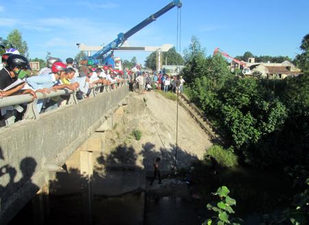 Rất đông người dân đứng trên thành cầu xem lực lượng cứu hộ cẩu xe lên