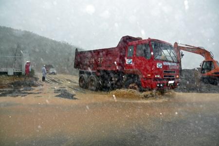 Các công nhân nỗ lực làm đường trong cơn mưa nặng hạt