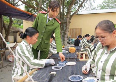 Nữ quản giáo hướng dẫn phạm nhân học nghề gia công đính hạt trên áo.
