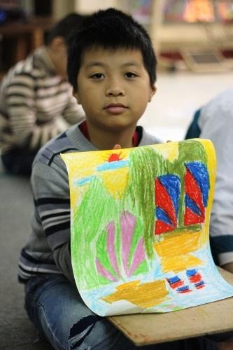 Một em khoe bức tranh đầy màu sắc của mình chuẩn bị được hoàn thành