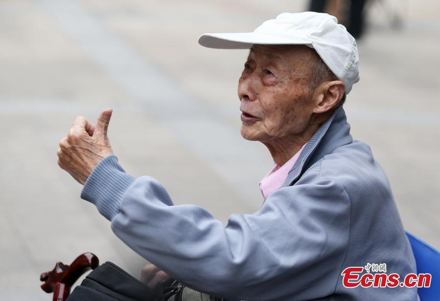 Cụ ông 86 tuổi làm dấu hiệu chiến thắng trước khi vào phòng thi.