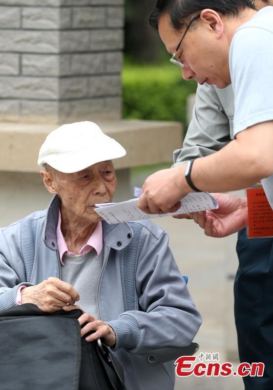 Thí sinh 86 tuổi chờđối chiếu thông tin trên thẻ dự thi. (Ảnh: China News Service)