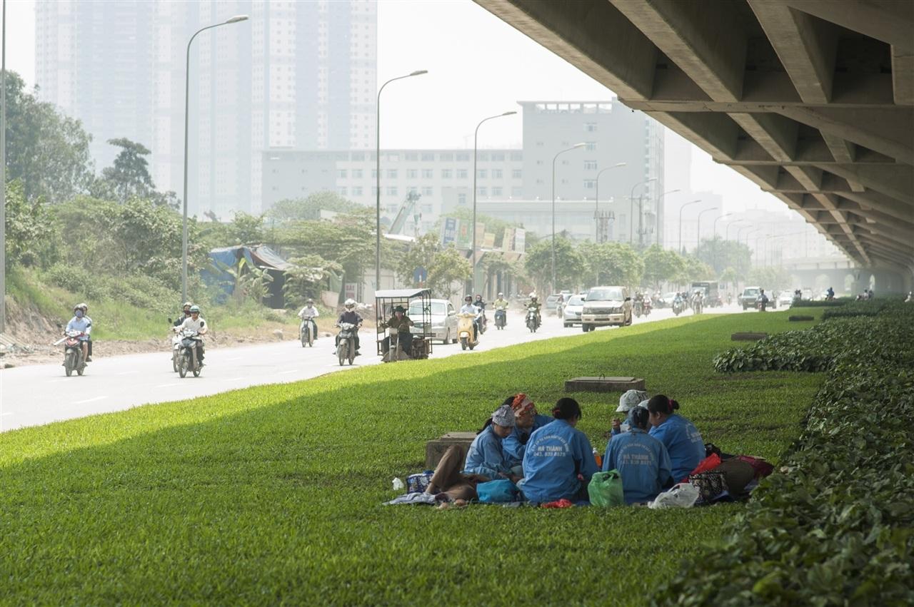 Công nhân tranh thủ tránh nắng trên các bãi cỏ