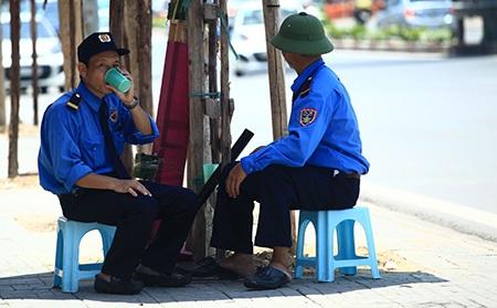 Chui gọn trong chiếc ô nhỏ là giải pháp tình thế của hai người bảo vệ trên đường Nguyễn Chí Thanh