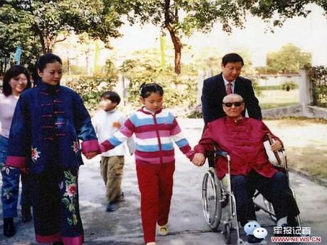 Tập Minh Trạch nắm tay mẹ và ông nội, trong khi ông Tập Cận Bình đang đẩy xe cho bố (Ảnh: