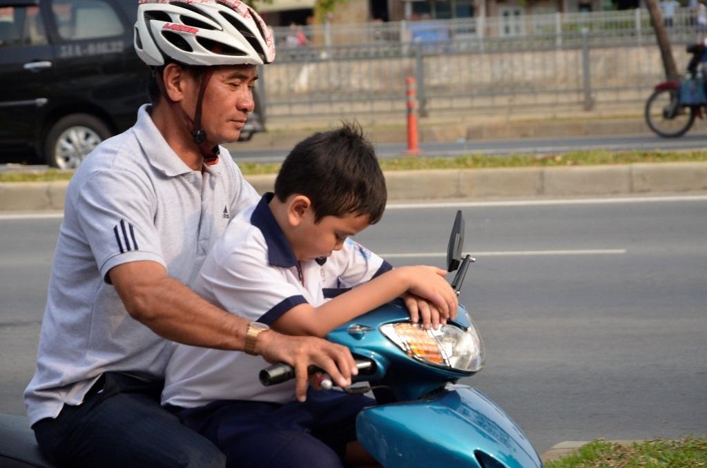Hình ảnh phụ huynh không đội MBH cho trẻ khi tham gia giao thông vẫn còn rất phổ biến