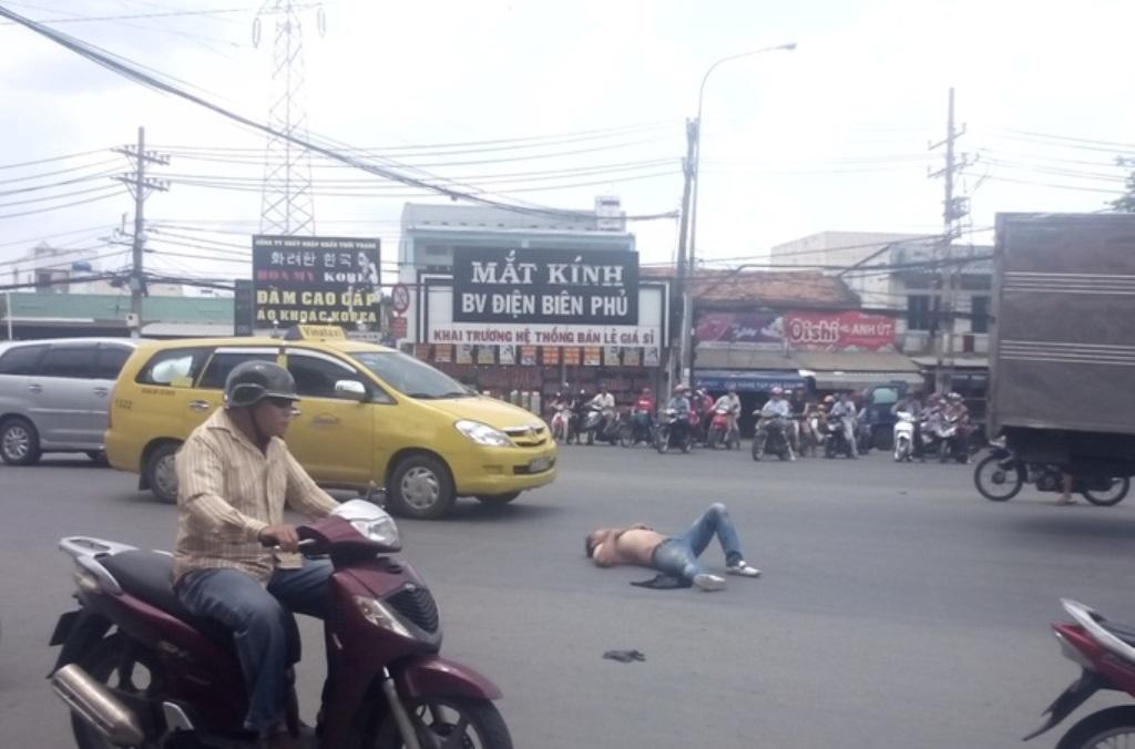 Thanh niên cởi áo nằm giữa đường