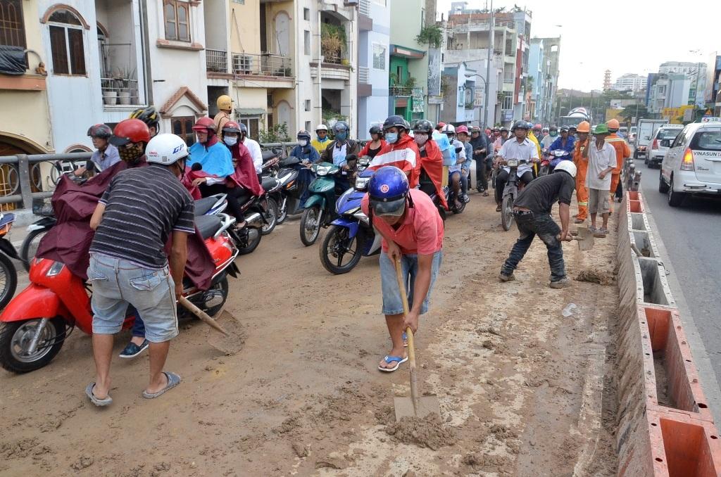 Các công nhân được huy động để xúc số bùn nhão trên đường