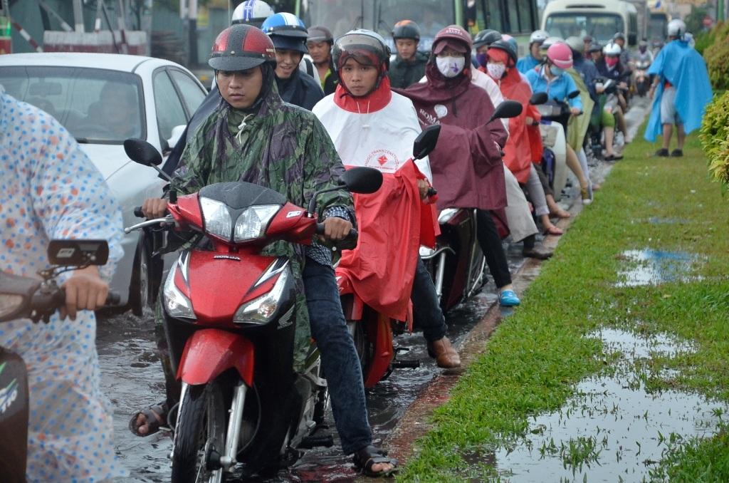 Dòng người di chuyển chậm giữa làn đường ô tô để tránh ngập