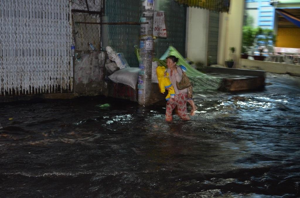 Người phụ nữ phải bồng bế 2 con nhỏ di chuyển trong nước ngập
