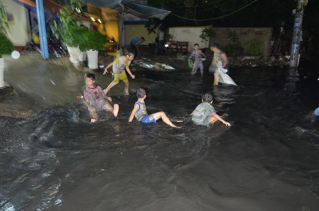 Nhiều em nhỏ vui đùa trong dòng nước đen ngòm