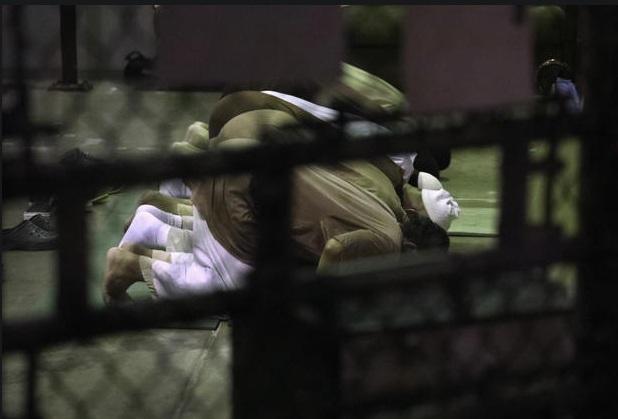 Hầu hết các tù nhân tại nhà tù Guantanamo là người Hồi giáo và nhiều người bị giam giữ tới 15 năm. Các tù nhân cầu nguyện 5 lần mỗi ngày. Phóng viên ảnh Moore cho hay thế giới của họ rất nhỏ nên nghi thức cầu nguyện là rất quan trọng. Trong ảnh, Moore chụp ảnh các tù nhân cầu nguyện thông qua tấm kính.