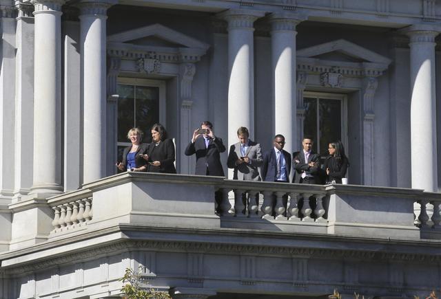 Mọi người đứng trên ban công một tòa nhà cạnh Nhà Trắng để quan sát.