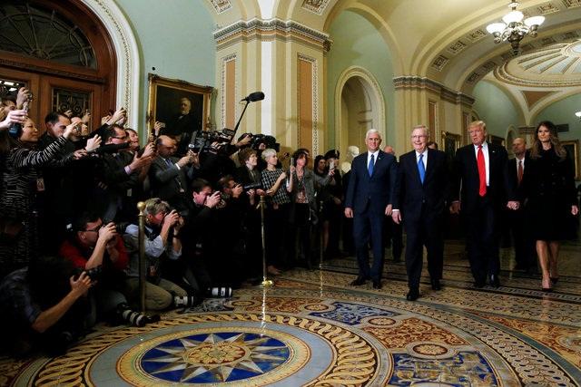 Vợ chồng ông Donald Trump nắm tay nhau khi thăm Điện Capitol trước sự chứng kiến của đông đảo phóng viên.