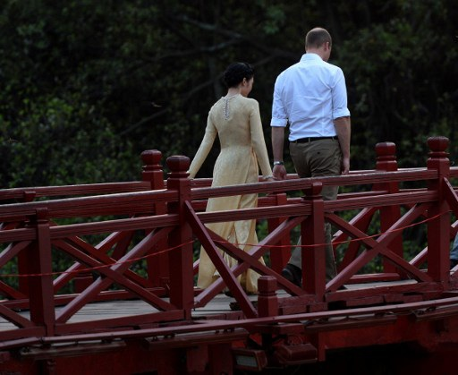 Sau khi rời phố Thuốc Bắc, Hoàng tử William tiếp tục di chuyển lên hồ Hoàn Kiếm và vào thăm đền Ngọc Sơn. Một nữ MC đi cùng Hoàng tử trên cầu Thê Húc, lối vào đền Ngọc Sơn. (Ảnh: AFP)