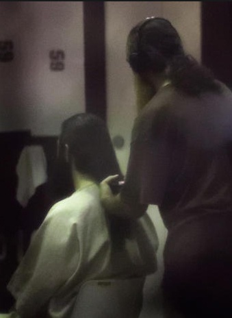 Tháng 10/2016, nhiếp ảnh gia John Moore của hãng Getty là một trong số ít các nhà báo được phép vào thăm nhà tù Guantanamo, được gọi tắt là Gitmo. Các bức đã được các quan chức báo chí kiểm tra và nhiều ảnh bị xóa vì các lý do như làm lộ mặt hay bất kỳ điều gì mà giới chức lo ngại là có thể ảnh hưởng an ninh. Trong ảnh, một tù nhân giúp một tù nhân khác buộc tóc trước một lễ cầu nguyện buổi tối.