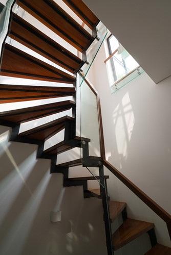 Thang bộ lớn, nặng nề và không tiện dụng được bố trí khéo léo để thêm vào một thang máy gia đình cỡ nhỏ bằng sắt và kính.