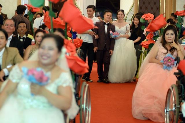 Các cô dâu, chú rể được dẫn lên sân khấu để làm lễ dưới sự chứng kiến và chúc phúc của người thân và bạn bè.