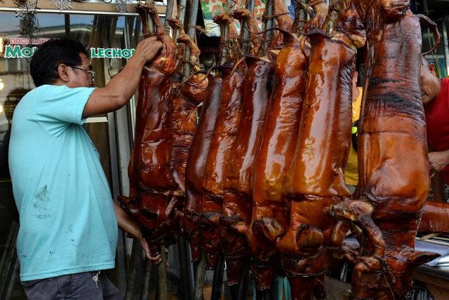 Một người đàn ông Philippines bận rộn chuẩn bị những con lợn quay, được người dân địa phương ưa thích trong bữa tiệc năm mới, tại một cửa hàng ở thủ đô Manila ngày 31/12. (Ảnh: Reuters)