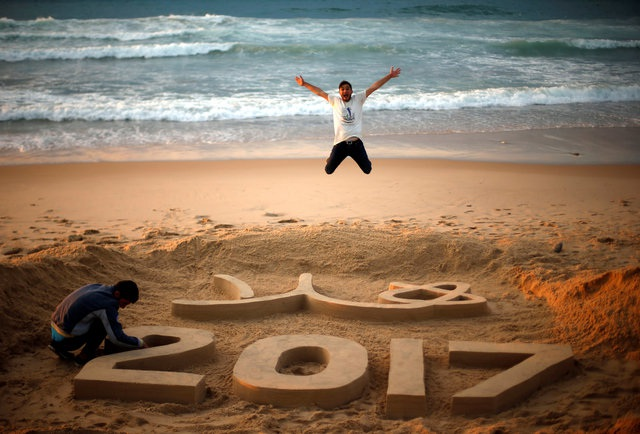 Nghệ sĩ Palestine Yazed Abu Jarad đang hoàn thành tác phẩm chào năm mới bằng cát, trong khi một người đàn ông thích thú với tác phẩm trên bãi biển ở Dải Gaza (Ảnh: Reuters)