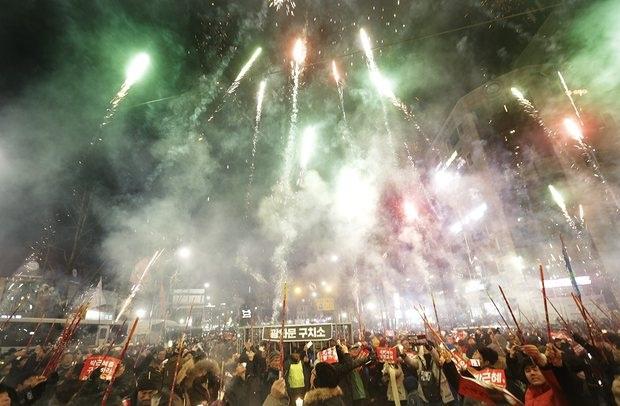 Người Hàn Quốc bắn pháo hoa trong cuộc biểu tình trong đêm yêu cầu Tổng thống Geun-hye từ chức (Ảnh: AP)