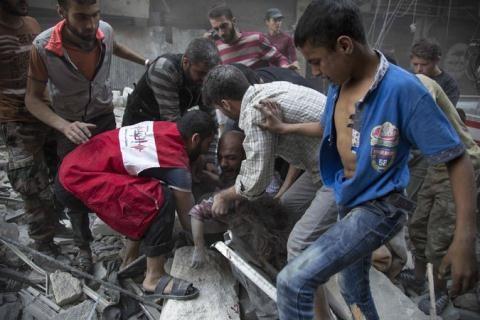 Người đàn ông khóc ôm cô con gái nhỏ bị vùi trong đống đổ nát sau trận bom tại Aleppo chiều thứ 3. Ảnh: The New York Times