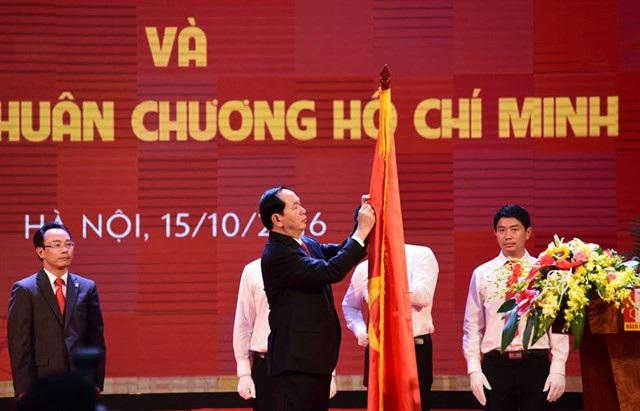 Chủ tịch nước Trần Đại Quang gắn Huân chương Hồ Chí Minh lên lá cờ truyền thống của ĐHBK Hà Nội