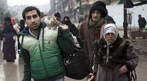 Người dân Syria rời khỏi một khu vực bị phiến quân chiếm giữ ở Aleppo ngày 13-12.