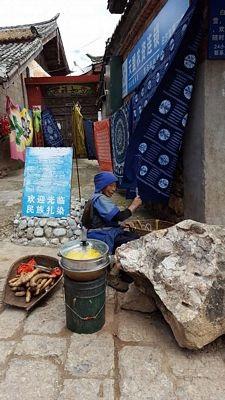 Người phụ nữ mặc trang phục Naxi truyền thống bán ngô luộc trong ngõ hẻm.