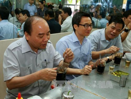 Thủ tướng Nguyễn Xuân Phúc và Phó Thủ tướng Vũ Đức Đam cùng các thành viên trong đoàn vi hành sáng 8/10, đã có bữa sáng bằng món phở và uống cả phê đá Sài Gòn (Ảnh: TTXVN)