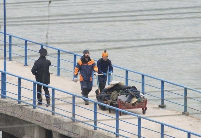 Các nhân viên cứu hộ đẩy chiếc xe chở các vật dụng của nạn nhân đượ tìm thấy (Ảnh: Reuters)