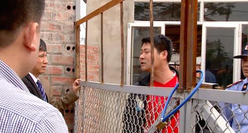 Người đàn ông áo đỏ xưng là Trưởng Công an xã Lão Hộ đang đứng trong nhà máy tuyên bố không cho ai vào nhà máy.