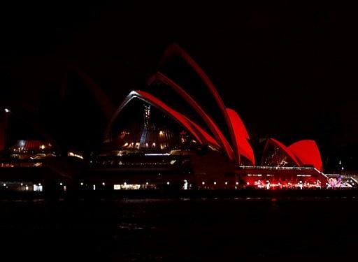 Nhà hát Opera tại Sydney, Australia được chiếu sáng màu đỏ trong đêm giao thừa. (Ảnh: AFP)