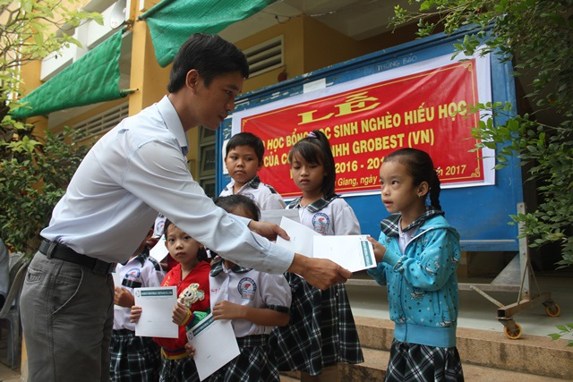 Ông Lê Văn Long, Trưởng đại diện khu vực Tiền Giang trao học bổng đến các em học sinh nghèo