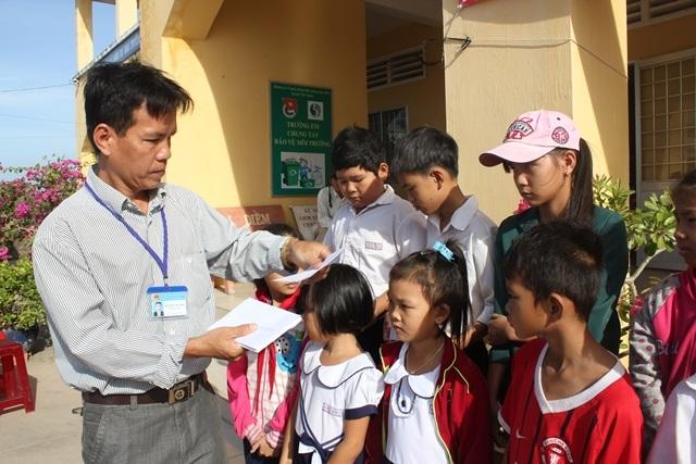 Đại diện Ban giám hiệu Trường tiểu học Vinh Kim A trao học bổng cho học sinh nghèo