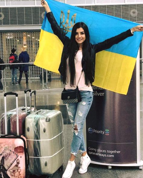 Hoa hậu Ukraine tạo dáng bên quốc kỳ và khá nhiều hành lý.
