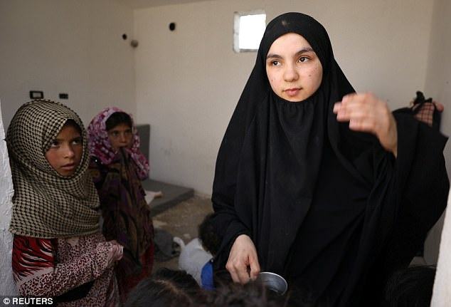 Những người vợ của các phiến quân IS đã hé lộ với các phóng viên về mối quan tâm lớn nhất của họ về đời sống hôn nhân. Đó là khoản tiền mà chồng mình chi để mua quần áo và mỹ phẩm cho các nô lệ tình dục. Trong ảnh: Một trong số những người vợ IS bị chính quyền Syria giữ lại khi đang cố vượt biên sang Thổ Nhĩ Kỳ. Họ bị tạm giữ biệt lập trong trại tị nạn Raqqa, Syria do có liên quan tới IS. (Ảnh: Reuters)
