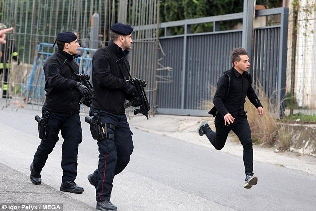 Một thanh niên chạy nhanh ra khỏi khu vực nguy hiểm trong khi hai cảnh sát đặc nhiệm sẵn sàng hành động.