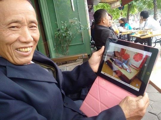 Ông Dương Văn Chuốt mở iPad khoe ảnh bà cả và bà thứ 6 nằm ngủ cùng nhau.