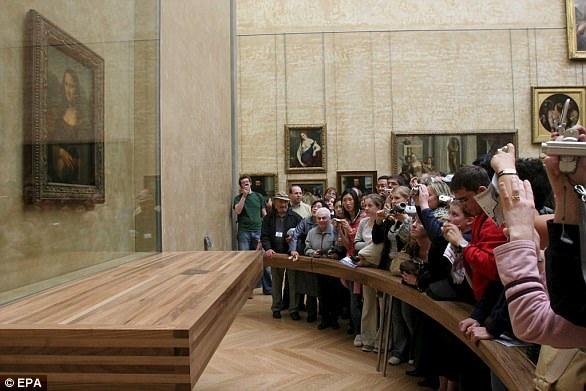 Khách du lịch đứng xung quanh chiêm ngưỡng bức nàng Mona Lisa tại bảo tàng Louvre ở Paris (Pháp).