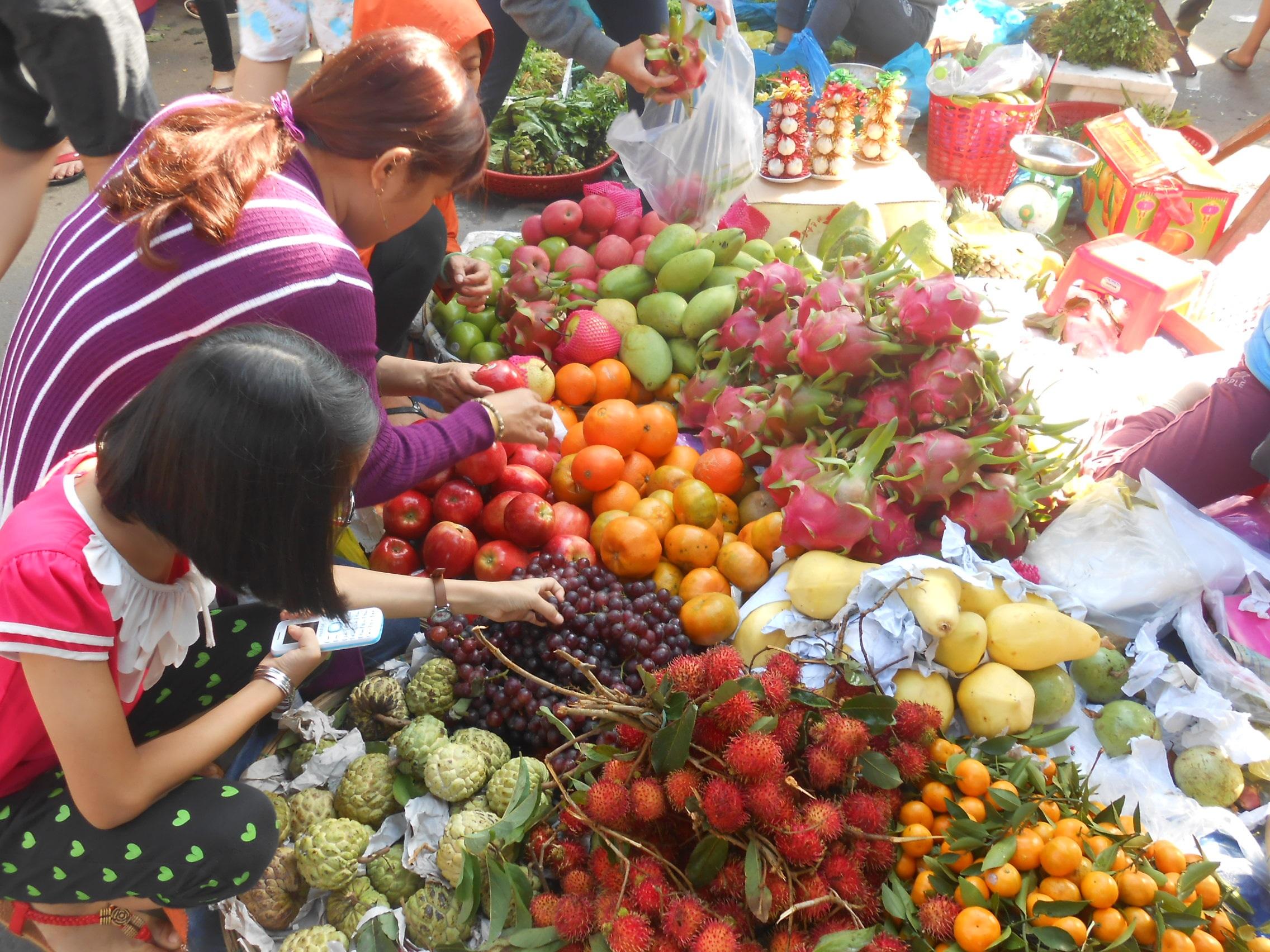 Người ta đi chợ cũng vì muốn gợi nhớ đến hương hoa quả đậm đà vị Tết
