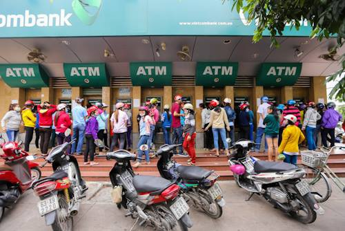 Dòng người tập trung trước trụ ATM ở khu chế xuất Tân Thuận, quận 7 chờ để rút tiền.