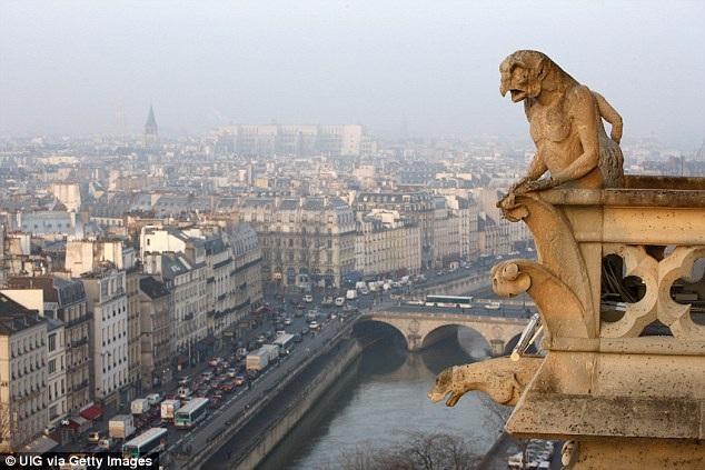Một bức tượng nằm trên một miệng máng xối của nhà thờ trông ra sông Seine.