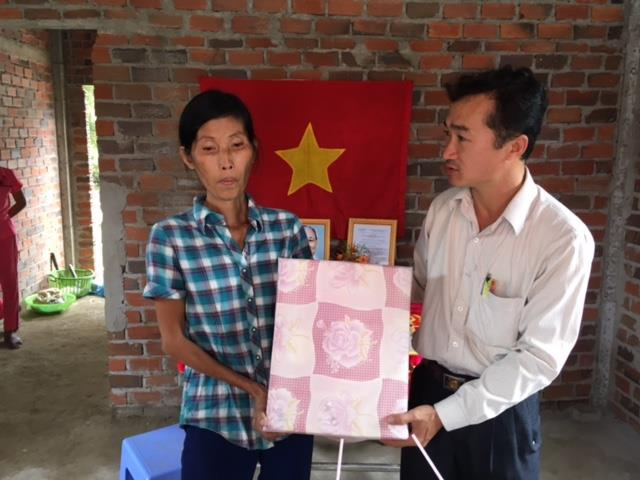 Đại diện lãnh đạo chính quyền địa phương trao quà cho gia đình bà Sương trong dịp khánh thành nhà