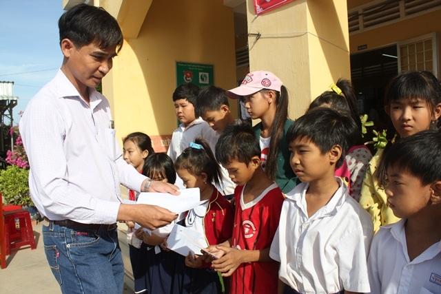 Ôg Nguyễn Đức Học, Giám đốc khu vực Công ty TNHH Grobest Việt Nam tại Trà Vinh trao học bổng đến các em học sinh nghèo vượt khó