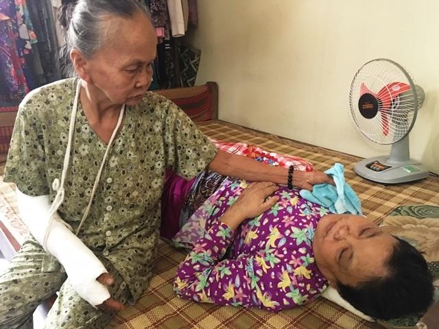 Còn 1 tay bà Nghĩa cũng ráng chăm sóc cho đứa con gái đang nằm liệt giường