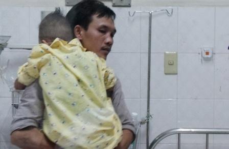 Người cha bế đưa con vào lòng cố xoa dịu những cơn đau do căn bệnh ung thư ác tính