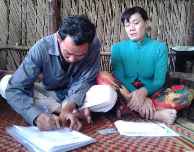 Vợ chồng anh Phạm Văn Thể ký nhận tiền hỗ trợ của bạn đọc báo Dân trí.