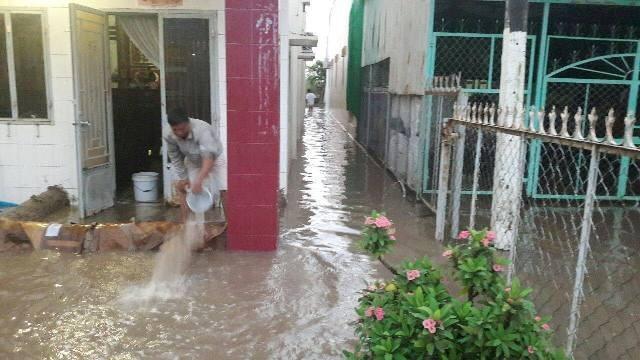 Người dân dùng bao cát, đất để ngăn nước vào nhà. Dùng xô tát nước ra ngoài...